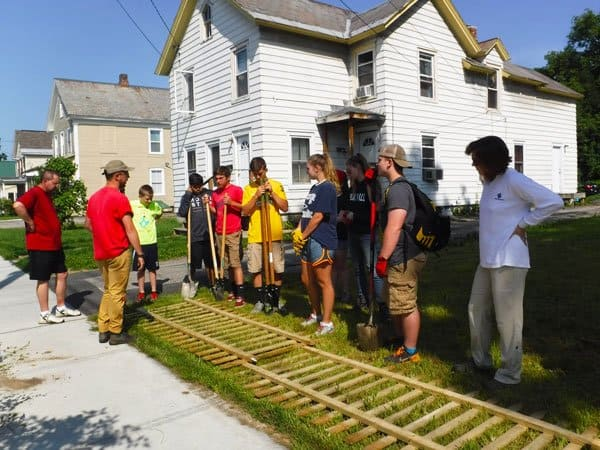 A team of young Northwest Rutland neighborhood volunteers installing a fence in Rutland, Vermont